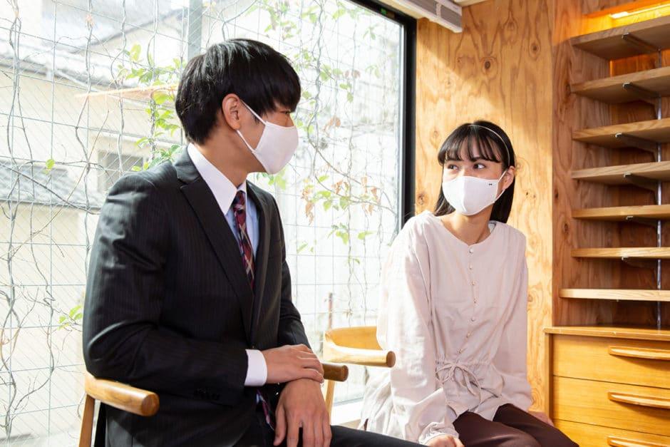日本製・オーガニックコットン生地の布マスクを付けて話す人